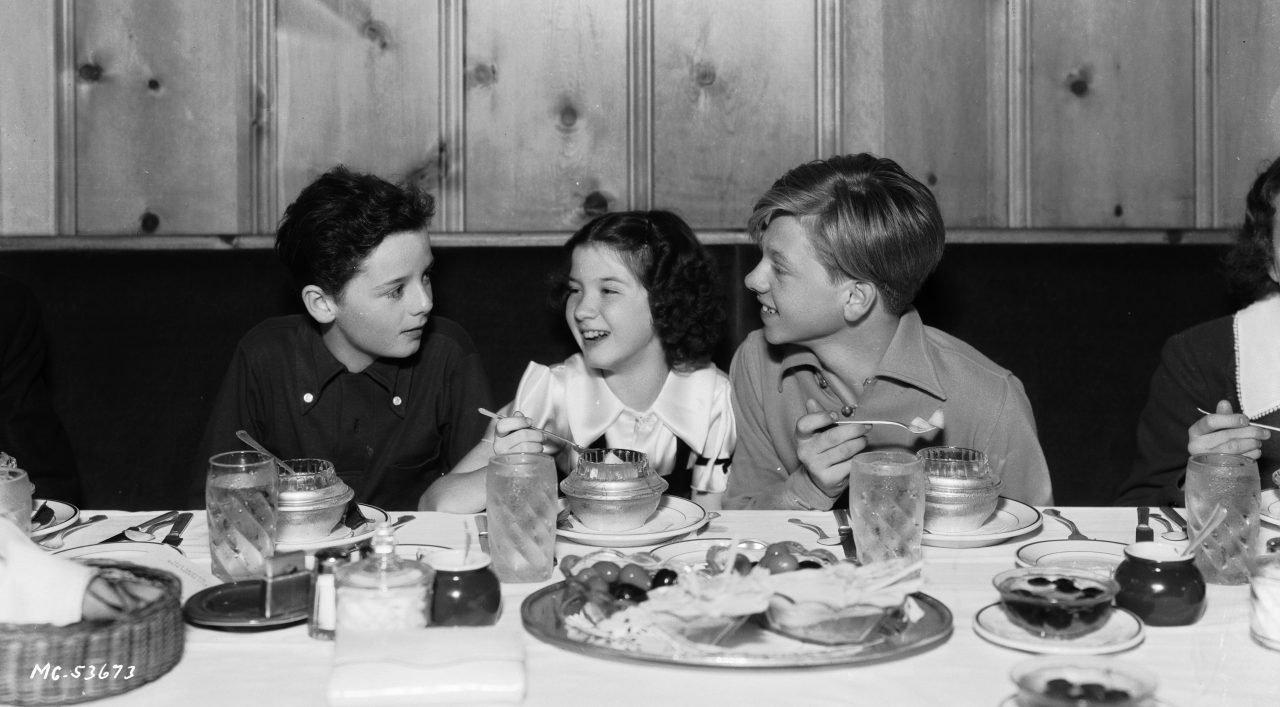 Niños en una mesa con comida.