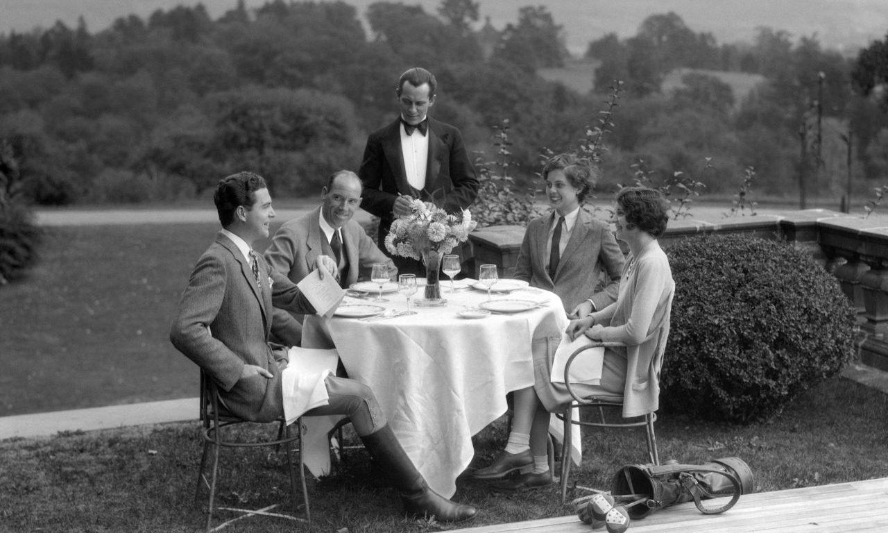 Gente elegante comiendo en una mesa al aire libre